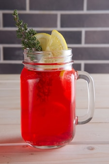 Xícara de suco de cranberry com frutas cítricas e alecrim