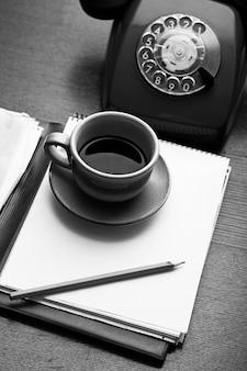 Xícara de telefone retro, notebook e café
