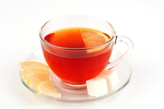 Xícara de vidro com chá e rodelas de limão. segure o copo à direita.