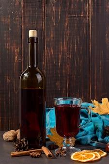 Xícara de vinho quente com especiarias, cachecol, folhas secas e laranjas em uma mesa de madeira. humor de outono, método para se aquecer no frio, copyspace.