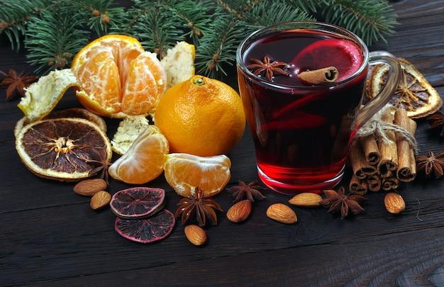 Xícara de vinho quente, especiarias e frutas cítricas em uma mesa de madeira.