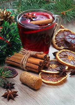 Xícara de vinho quente, especiarias e frutas cítricas secas em uma mesa de madeira.