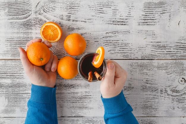 Xícara de vinho quente quente e laranjas na guia de madeira