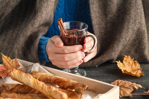Xícara de vinho quente quente na mão feminina