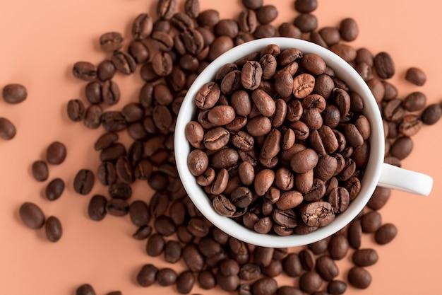 Xícara de vista superior com grãos de café orgânicos
