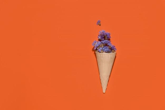Xícara de waffle para sorvete com flores azuis em um espaço laranja. copie o espaço