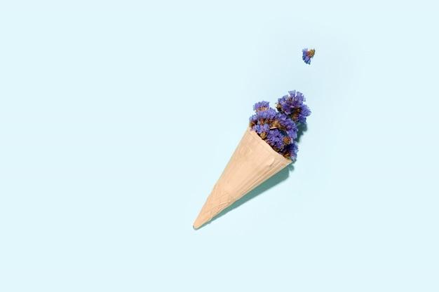 Xícara de waffle para sorvete com flores em um espaço azul. copie o espaço. conceito de verão