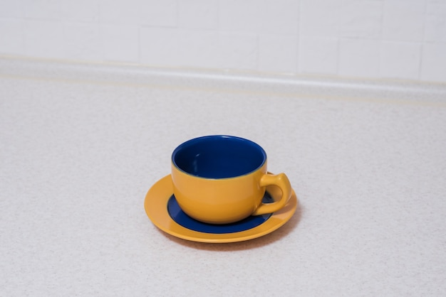 Xícara e pires azuis amarelos na mesa da cozinha.