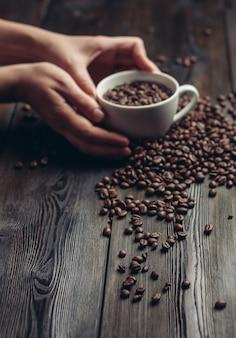 Xícara e pires de grãos de café em um aroma de fundo de madeira