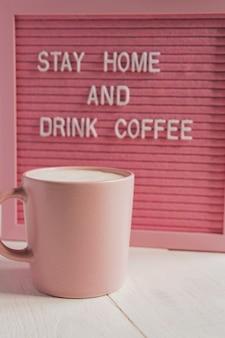 Xícara e xícara de café rosa fique em casa e beba café. campanha de auto-isolamento e quarentena.