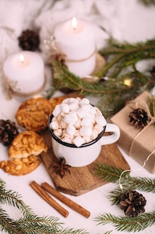 Xícara esmaltada de chocolate quente ou café com marshmallows e biscoitos. em torno dos galhos das árvores, presentes e velas acesas. espírito de natal. cartão postal ou fundo de inverno.