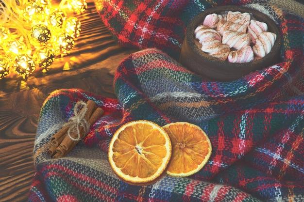 Xícara grande de chocolate quente com marshmallow, canela e laranja seca e cobertor quente em um velho vintage de madeira e luz de natal. arranjo acolhedor de natal ou outono.