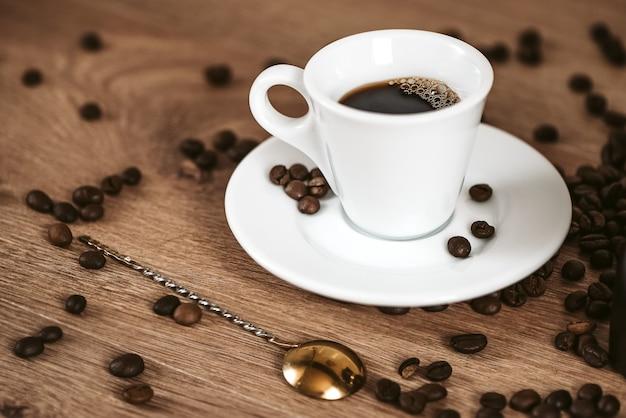 Xícara pequena branca de café expresso fresco na superfície da mesa com grãos de café torrados espalhados