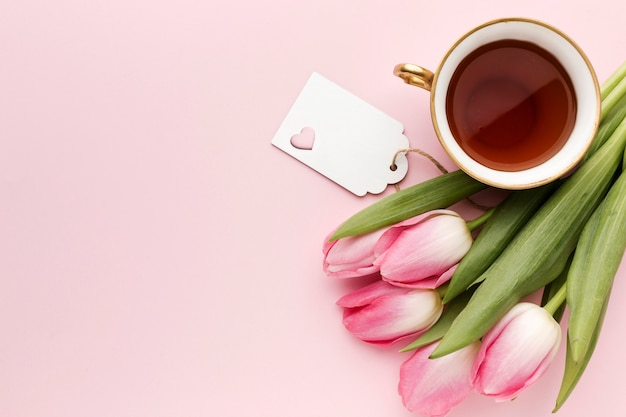 Xícara plana leiga com chá ao lado de tulipas