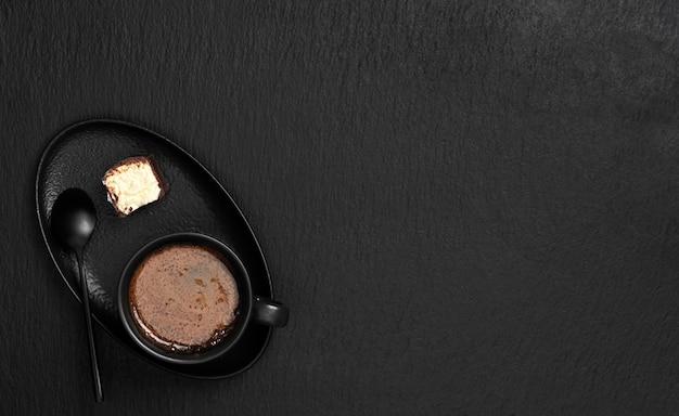 Xícara preta com café expresso, em um pires, uma sobremesa e uma colher