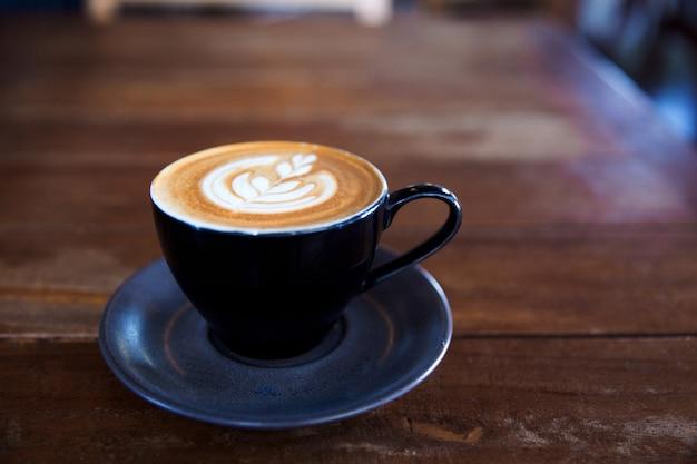 Xícara preta de cappuccino quente na placa texturizada azul no fundo da mesa de madeira com latte art.