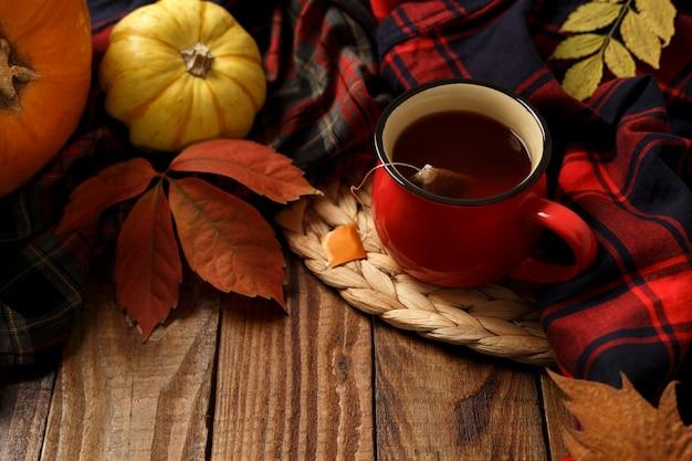 Xícara quente de chá e abóboras