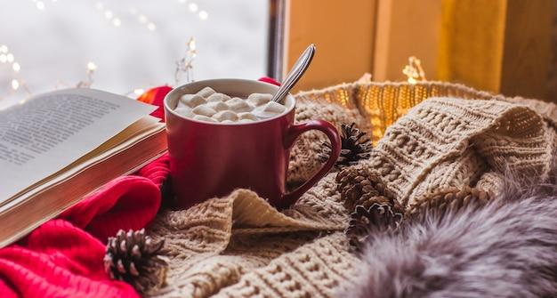 Xícara vermelha com chocolate e marshmallows em uma mesa de madeira com lenços de livro antigo conforto de casa