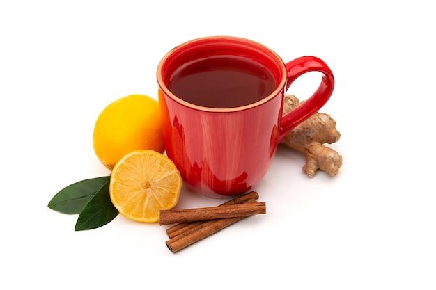 Xícara vermelha de chá preto ou verde quente com limão e gengibre em um fundo branco. ingredientes contra influenza e vírus. medicina natural.