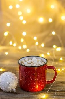 Xícara vermelha de chocolate quente com bolinhas brancas de marshmallows e bastões de doces