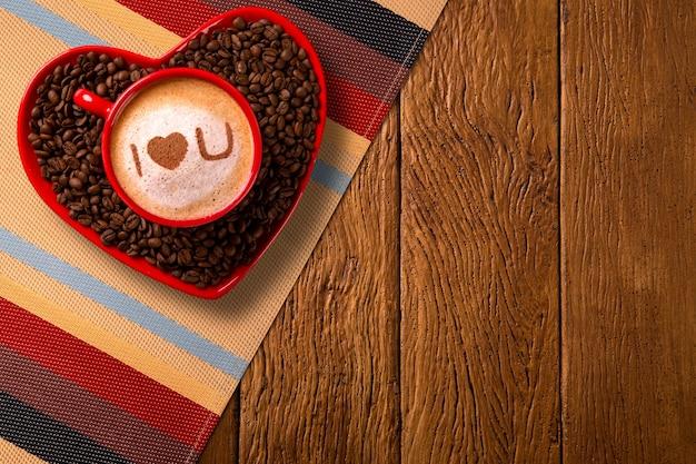 Xícara vermelha e pires de café em forma de coração com café decorado em fundo de madeira velho. vista do topo. escrito eu te amo forma no café em inglês.