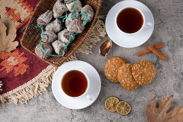 Xícaras brancas de chá quente com frutas secas e biscoitos de aveia sobre uma mesa de pedra.