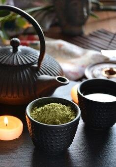 Xícaras cheias de chaleira japonesa de água quente e incenso e velas