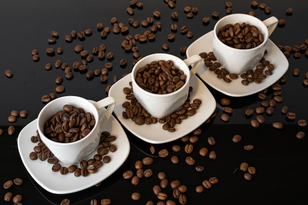Xícaras com grãos de café torrados em mesa preta