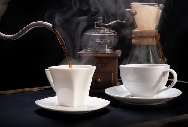 Xícaras de café a vapor com moedor de café, cerveja e chaleira no fundo escuro da mesa de madeira de grunge