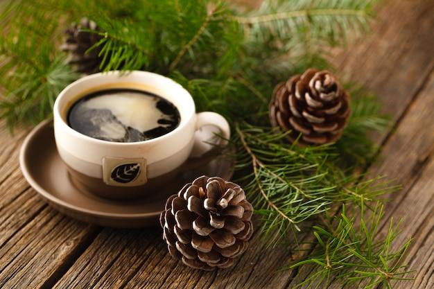 Xícaras de café ao lado de cones e um ramo de pinheiro