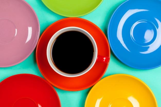 Xícaras de café coloridas e pires em colorido vibrante