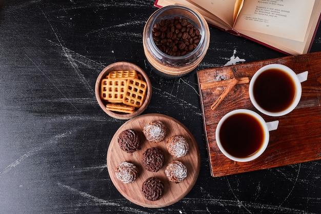 Xícaras de café com biscoitos e bombons.