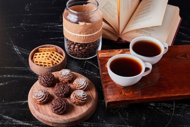 Xícaras de café com grãos e bombons de chocolate.
