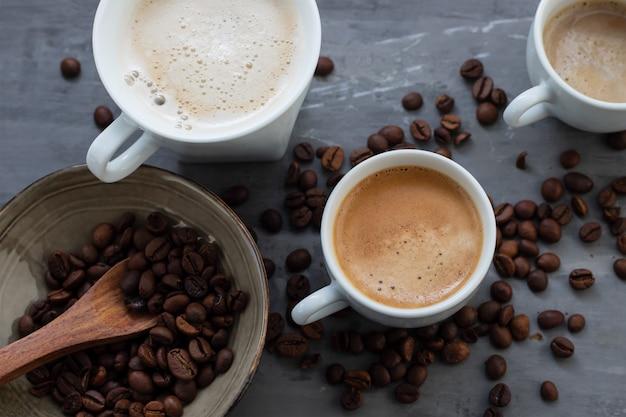 Xícaras de café com leite e grãos em fundo de cerâmica