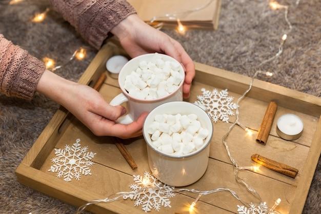 Xícaras de café com marshmallow na bandeja de natal, foco suave