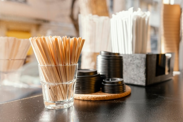 Xícaras de café com tampas e palitos de madeira no balcão da cafeteria