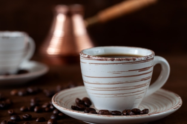 Xícaras de café e turco de cobre na mesa