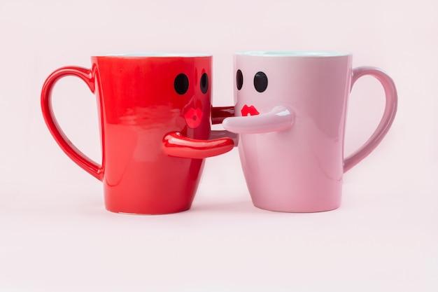 Xícaras de café em um fundo rosa com um sorriso na caneca, abraçando-se.