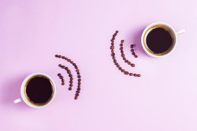 Xícaras de café expresso com sinal wi-fi de grãos de café em fundo rosa