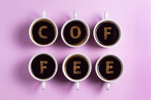Xícaras de café expresso em um fundo rosa com a inscrição de café