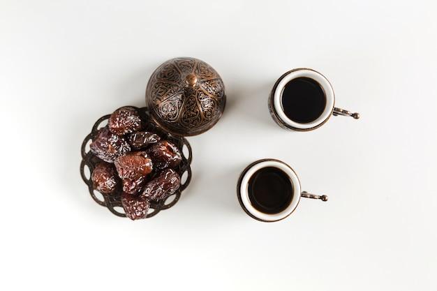 Xícaras de café perto de pires com ameixas