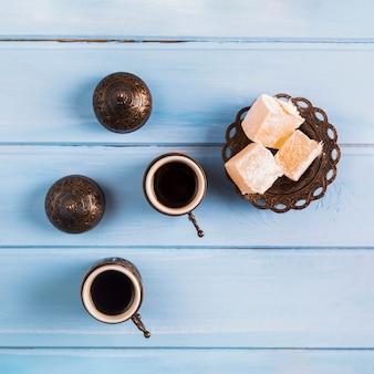 Xícaras de café perto de pires com delícias turcas
