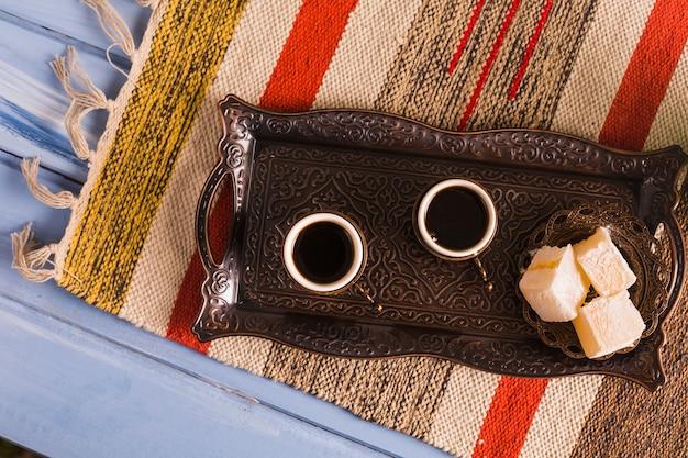 Xícaras de café perto de pires com doces delícias turcas na bandeja contra o tapete