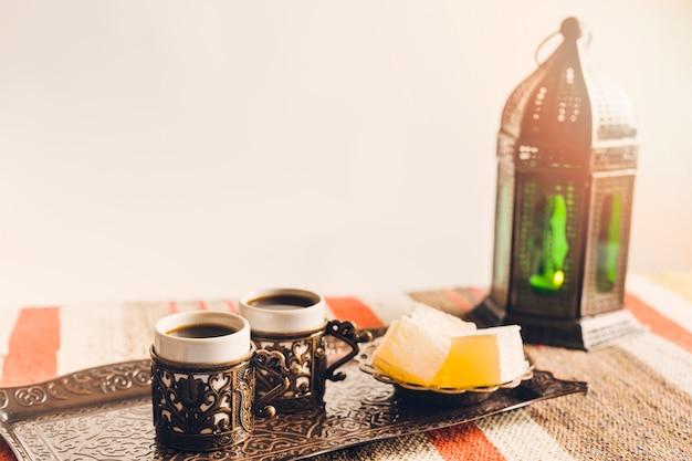 Xícaras de café perto de pires com doces delícias turcas na bandeja e lanterna