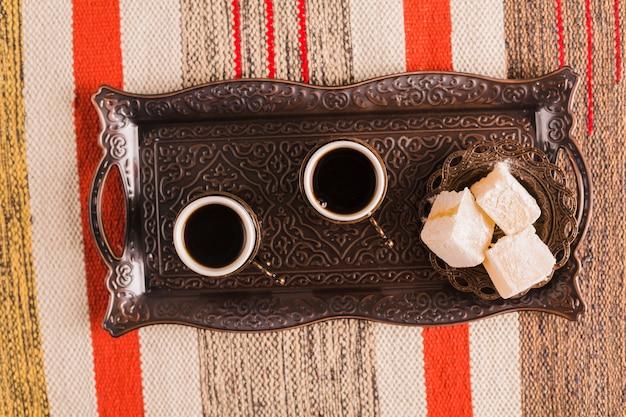 Xícaras de café perto de pires com doces delícias turcas na bandeja