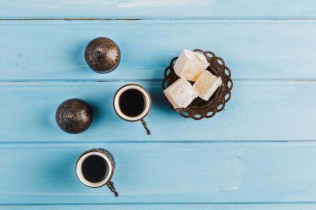 Xícaras de café perto de pires com doces doces delícias