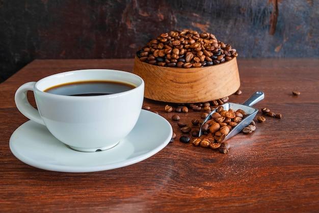 Xícaras de café preto e grãos de café torrados em uma mesa de madeira