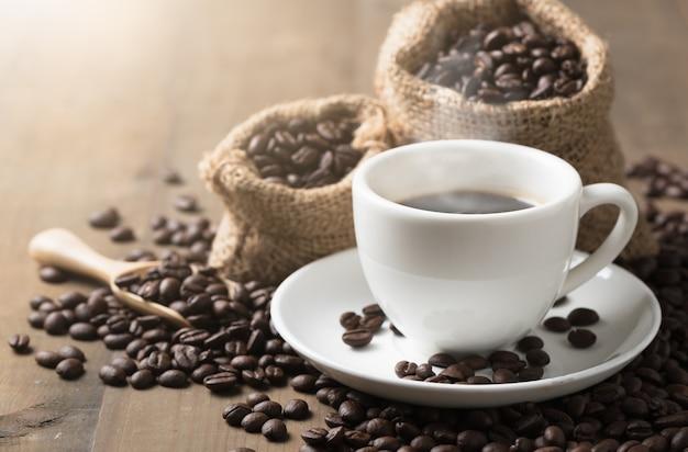 Xícaras de café quente com fumo e grãos de café sobre fundo de madeira velho