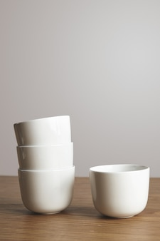 Xícaras de café simples brancas em forma de vista lateral em forma reta em pirâmide na mesa de madeira grossa isolada