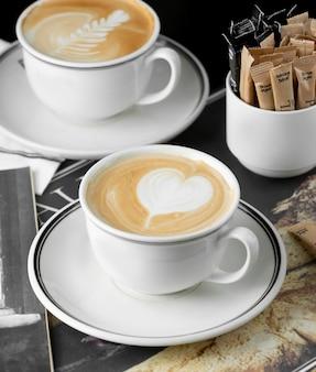 Xícaras de cappuccino com coração e rosetta latte art